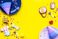 Baby shower. Cookies in shape of accesssories for child, party hats and confetti on yellow background top view copy. Baby shower. Cookies in shape of royalty free stock image