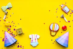 Baby shower. Cookies in shape of accesssories for child, party hats and confetti on yellow background top view copy. Baby shower. Cookies in shape of stock photography