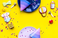 Baby shower. Cookies in shape of accesssories for child, party hats and confetti on yellow background top view copy. Baby shower. Cookies in shape of stock photos