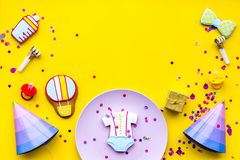 Baby shower. Cookies in shape of accesssories for child, party hats and confetti on yellow background top view copy. Baby shower. Cookies in shape of royalty free stock images
