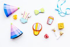Baby shower. Cookies in shape of accesssories for child and party hats on white background top view.  stock images