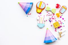 Baby shower. Cookies in shape of accesssories for child and party hats on white background top view copy space. Baby shower. Cookies in shape of accesssories for royalty free stock images