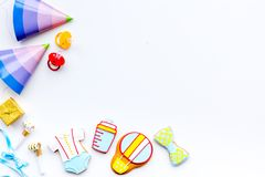 Baby shower. Cookies in shape of accesssories for child and party hats on white background top view copy space. Baby shower. Cookies in shape of accesssories for stock image