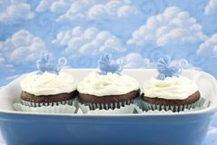 Baby Shower Cupcakes for Boy. Chocolate with vanilla frosting with baby carriage decoration, blue sky and cloud background, selective focus, copy space royalty free stock image