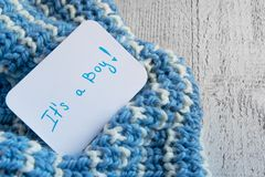 Baby shower` det ` s en pojke`, meddelandekort på den hemtrevliga woolen blåa filten och utrymme för text Ny ankomst i familjen arkivbilder
