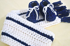 Baby shower gift for newborn boy. Baby shower gift - crochet baby boy shoes and scarf royalty free stock photo