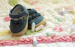 Baby Shower Invitation. Denim baby shoes with tiny baby bottles on a light pastel background greeting card space  boy girl Royalty Free Stock Photography