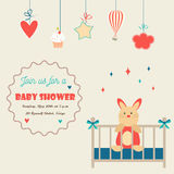 Baby shower invitation card with little rabbit in a baby cot Stock Photos