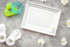 Baby shower modern design with frame on gray stone background to. Baby shower modern design with frame, clothes and toys on gray stone background top view mockup stock photos