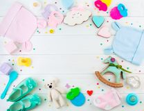 Frame from baby clothes and accessories on white wooden background with copy space. Baby shower party background: frame from baby clothes and accessories on royalty free stock photo