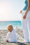Baby showing mother something on beach. Baby girl showing mother something on beach. Rear view Royalty Free Stock Photos