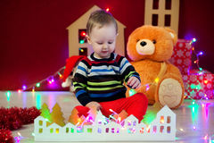 Baby sit on background of a garland of lights, teddy bears and toy houses and plays Royalty Free Stock Photography