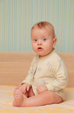 Baby sit on a cot. At home Stock Photo