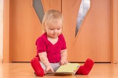 Baby sit on floor and read baby book Stock Photography