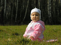 Baby sit on grass. In jacket and hat stock photo