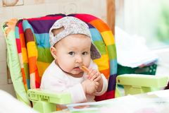 Baby sit in highchair and eats royalty free stock photography