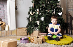 Baby sit near decorating Christmas tree with present boxes Stock Photos