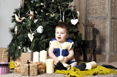 Baby sit near decorating Christmas tree with present boxes Stock Image