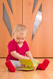 Baby Sit On Floor And Read Baby Book Royalty Free Stock Image
