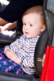 Baby sit in safety car seat. Cute little girl in car seats in car. Portrait of pretty toddler girl sitting in car seat. stock photo