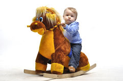 Baby sit on wooden toy horse in studio Stock Photos