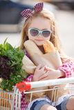 The baby sits in a basket with food near the shopping center. Royalty Free Stock Images