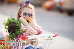 The baby sits in a basket with food near the shopping center. Royalty Free Stock Photography