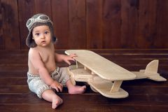 Baby sits on the floor next to the wooden plane Stock Photography