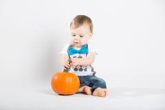 Baby Sits Grabbing Stem of Pumpkin Royalty Free Stock Photography