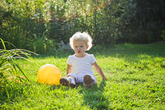 Baby sits on a grass royalty free stock photography