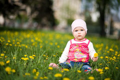 Baby sits on a green grass in dandelions Royalty Free Stock Photography