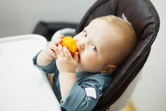 Baby sits in highchair and eats peach stock photos