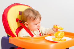 Baby sits in  highchair with orange. Baby sitting in highchair and eats an orange Stock Photography