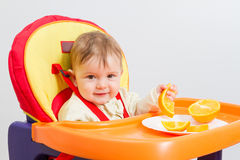 Baby sits in  highchair with orange. Baby sitting in highchair and eats an orange Stock Photos