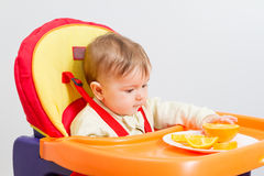 Baby sits in  highchair with orange. Baby sitting in highchair and eats an orange Royalty Free Stock Images