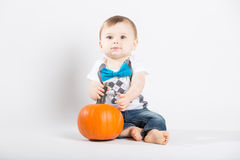 Baby Sits and Looks Up with Pumpkin. A cute 1 year old sits in a white studio setting with a pumpkin. The boy looks up while holding the stem of the pumpkin. He Royalty Free Stock Images