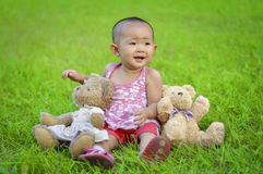A baby sits in meadow. A chinese baby sits in meadow Royalty Free Stock Photos