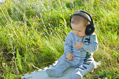 Baby sits on a meadow with headphones Stock Photo