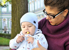 Baby sits on mother lap and eats corn ball. Baby sits on mother and eats corn ball Stock Image