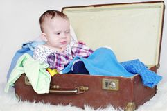 Baby sits in an old suitcase Stock Image