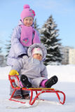 Baby sits on sled and little sister stands behind him Royalty Free Stock Images