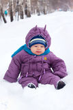 Baby  sits in the snow. A little boy, baby  sits in the snow, snowball Royalty Free Stock Photography