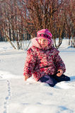 Baby sits on snow and looks Stock Image