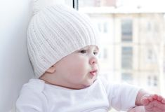 Baby sits at a window overlooking the next house Royalty Free Stock Photo