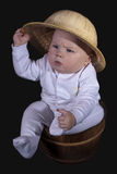 The baby sits in a wooden bucket Stock Image