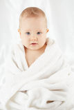 Baby sits wrapped in bath towel Stock Photo