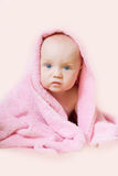Baby sits, wrapped in a pink towel Stock Photo