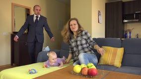 Baby-sitter colocado no sofá perto do bebê Homem irritado do pai no terno 4K video estoque