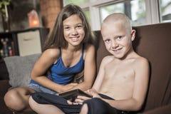 Baby-sitter com um techno do sofá da criança Imagem de Stock Royalty Free