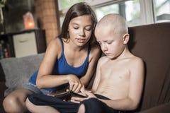 Baby-sitter com um techno do sofá da criança Fotos de Stock Royalty Free